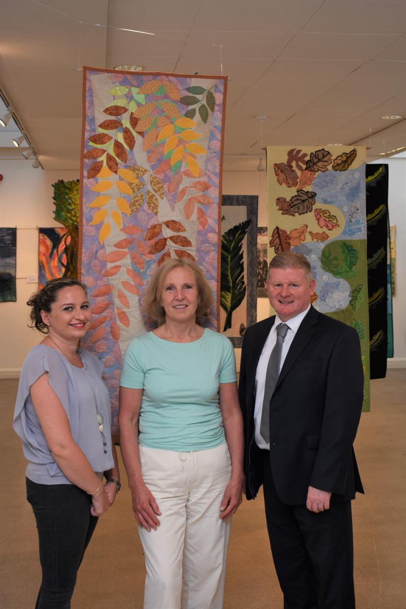 Cllr and staff at wall of collection of quilts