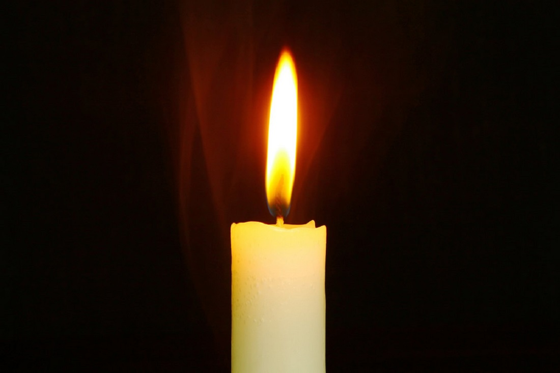 image of lit candle on black background