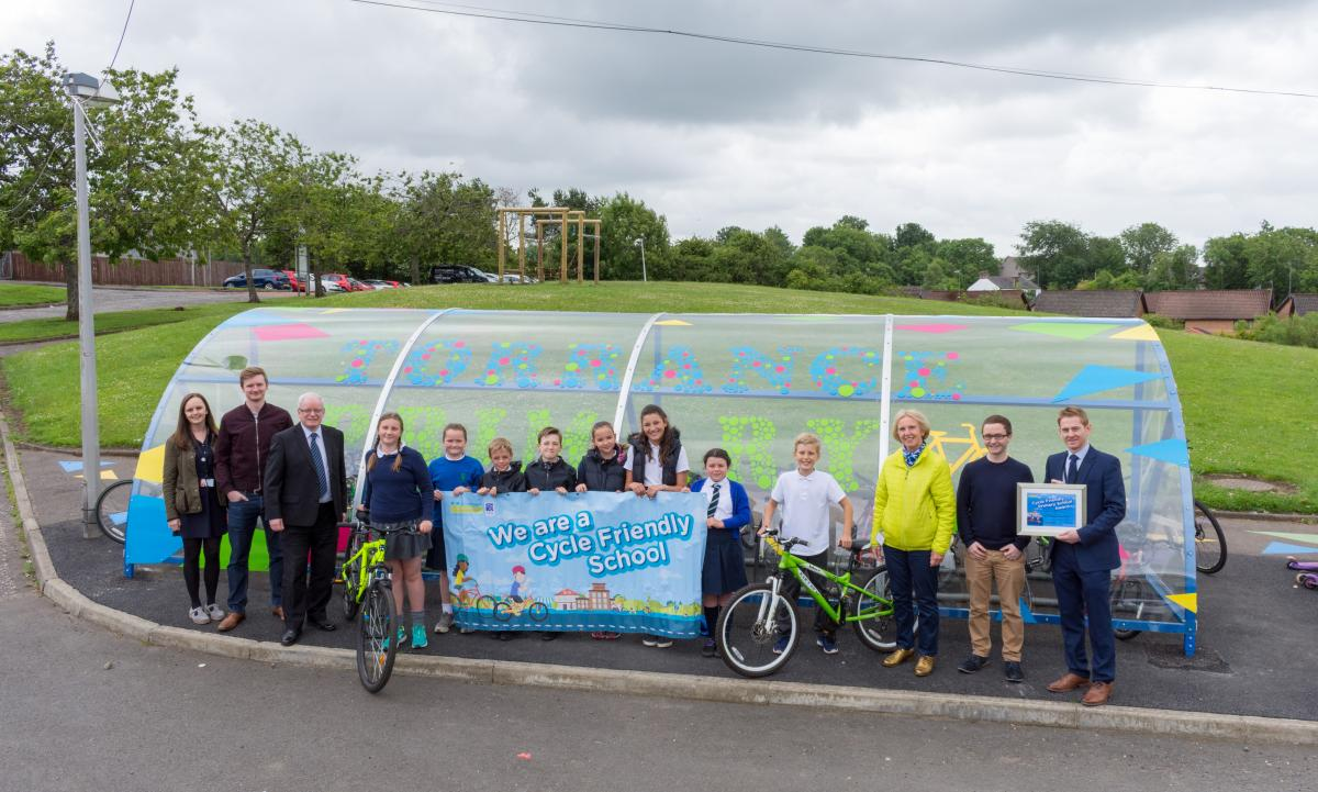 adults and children with poster of cycle friendly school banner